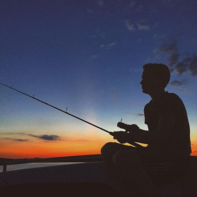 silhouette of a person with a fishing pole with the sunset behind them