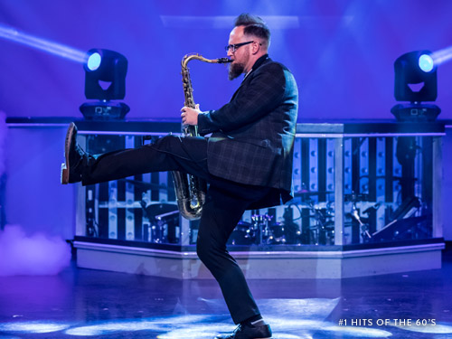 Performer playing saxophone on a Branson live show stage.