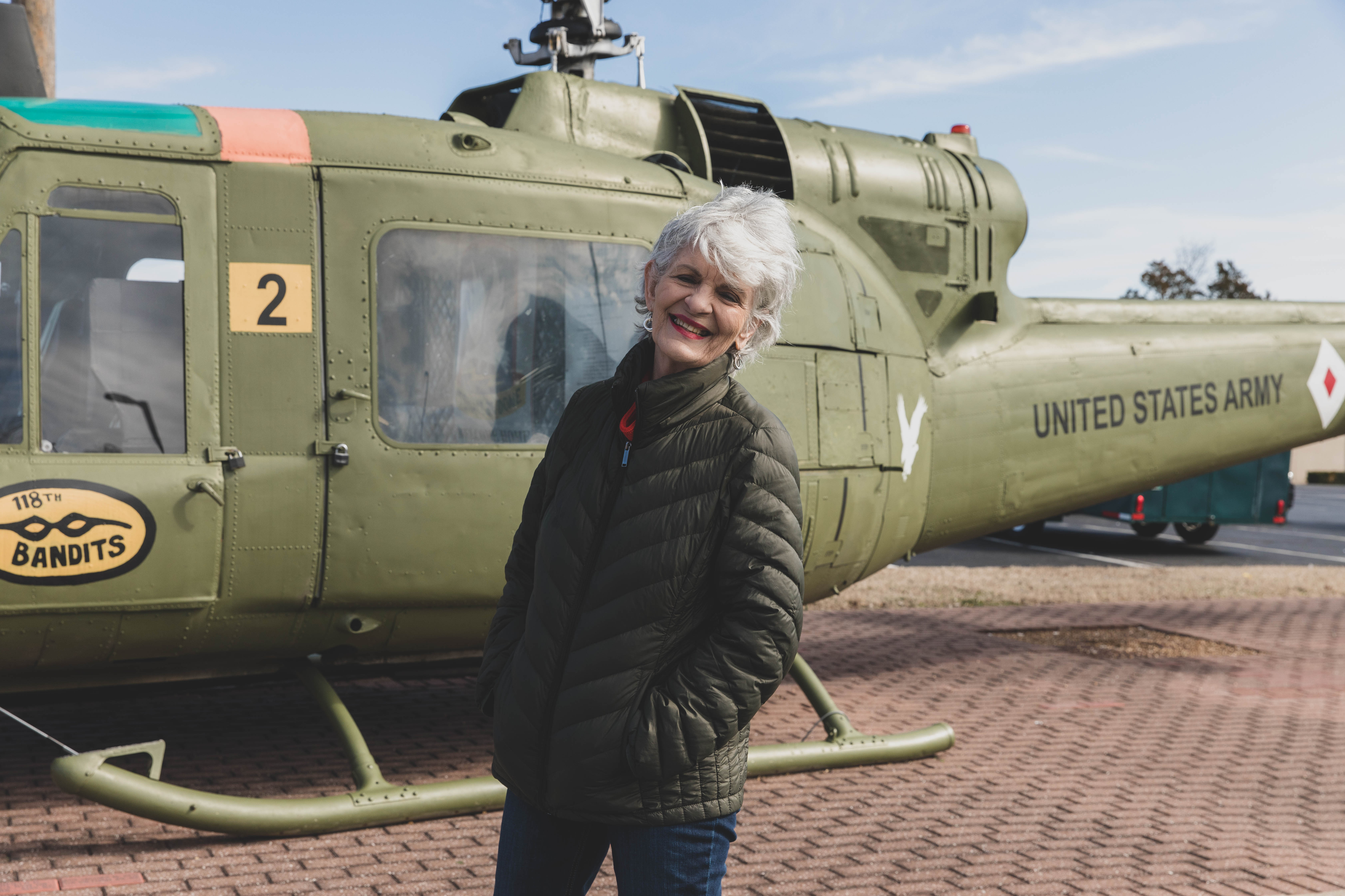 Vietnam Veteran woman standing in front of an army helicopter.