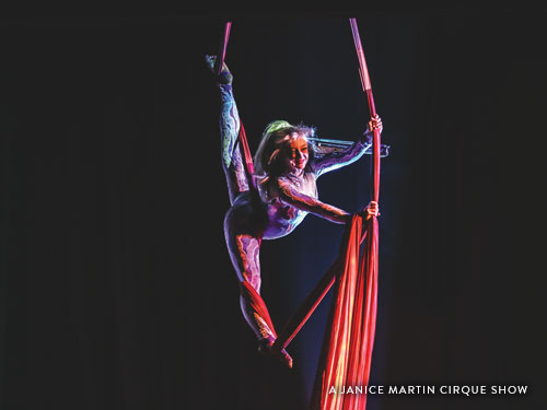 Women flying on areal ropes during a Branson cirque show.