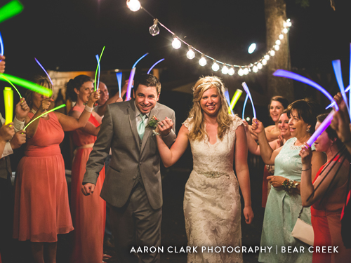 Couple leaving wedding surrounded by sparklers, friends and family.