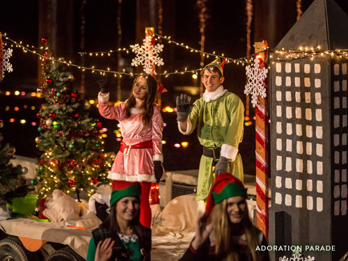 Two Christmas elves waving to guests from a parade float.