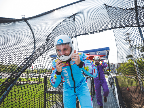 Aerodium instructor wearing a blue jumpsuit about to take flight on an outdoor skydiving aerodium
