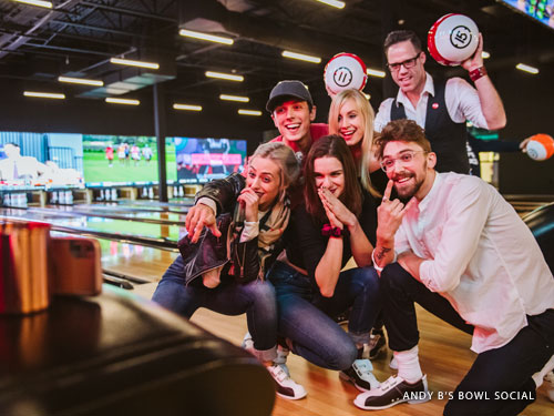 Group of young adults taking a selfie at a bowling attraction in Branson.