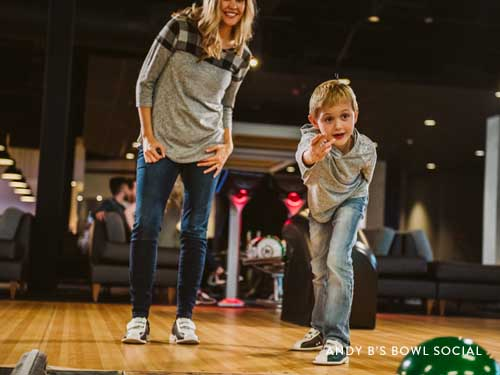 Mom and son throwing bowling ball down the lane.