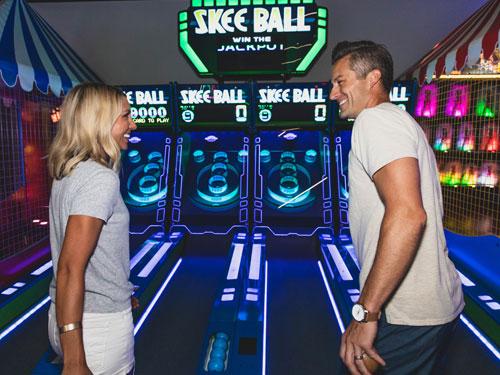 Couple playing skee ball at Bigfoot arcade.