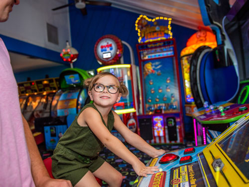 Father and daughter playing games in an indoor Branson arcade.