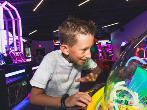Young boy playing arcade game at Bigfoot Arcade.