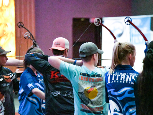 Group of students shooting archery in a state tournament.