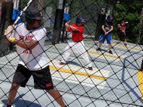 Young boys swinging a baseball bat in a Branson batting cage.