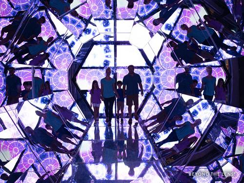 Family of four walking through a lifesize kaleidoscope in Branson.