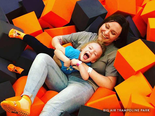 Mother and daughter laying in foam block pit in a trampoline park in Branson.