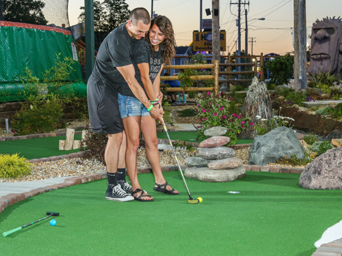 Man and woman playing mini golf at an outdoor course in Branson.