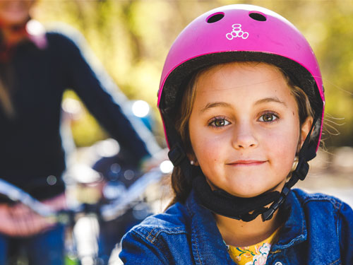 young girl wearing pink helmet and riding a bike with her mom in a nature park in Branson.