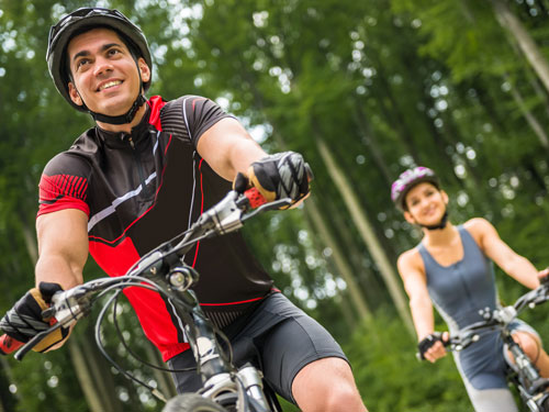 Man and woman wearing helmets and riding bicycles on a tree-lined trail in Branson.