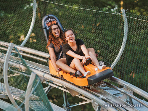 Two girls riding inside a mountain coaster car on a track in Branson.