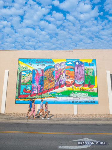 Family of four walking in front of a colorful Downtown Branson mural.