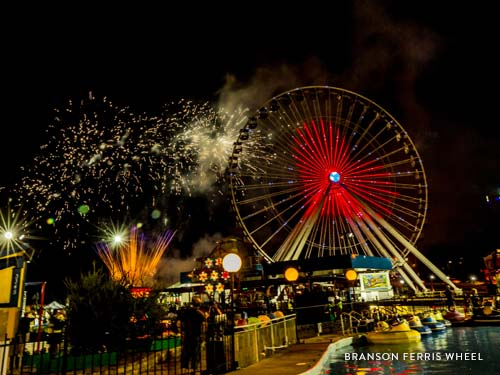 Branson Ferris Wheel lit up by 16,000 LED lights at night shaped like a heart and surrounded by fireworks.