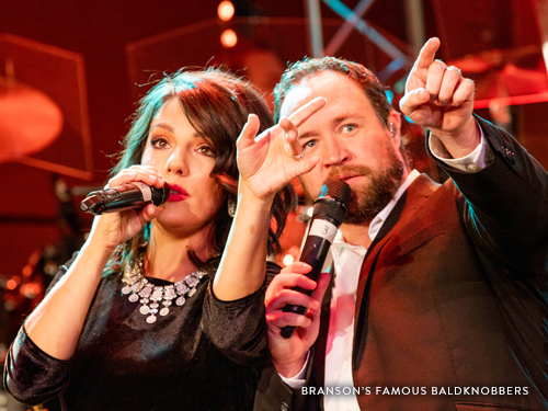 Husband and wife singing on a Branson live show stage.