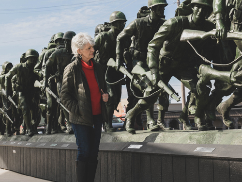 Woman Army veteran looking at a monument of fellow soldiers in Branson.