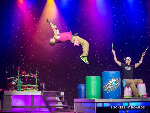 Two men drumming on buckets and boards on a live show stage in Branson.