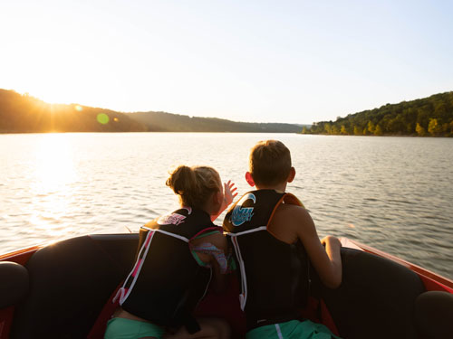 Brother and sister looking out at the lake from their family boat in Branson.
