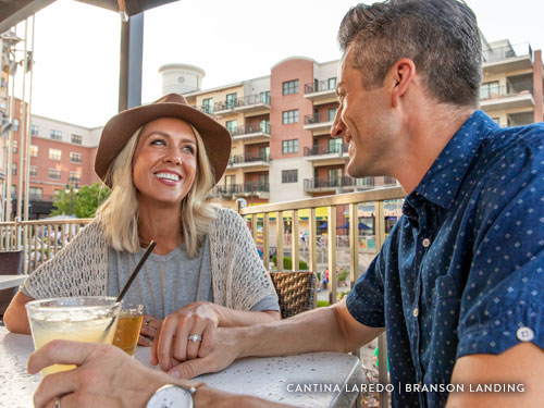 Couple holding hands during a meal at Branson Landing.
