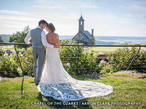 Newlyweds hugging in front of a large chapel on an Ozark golf course.