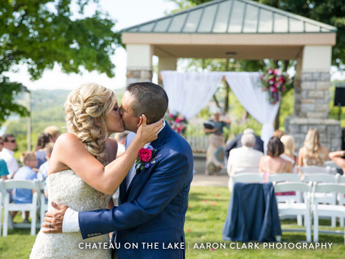 Newlywed couple kissing at the end of the aisle after their outdoor wedding ceremony.