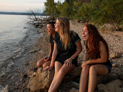 Three girls sitting on a lake shoreline on rocks while staring into the sunset and laughing in Branson.