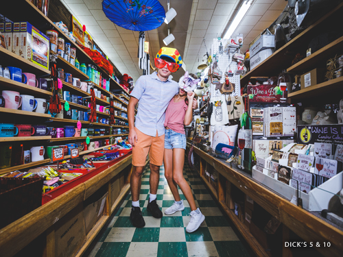 Brother and sister shopping in a novelty store and wearing funny hats and glasses in Downtown Branson.