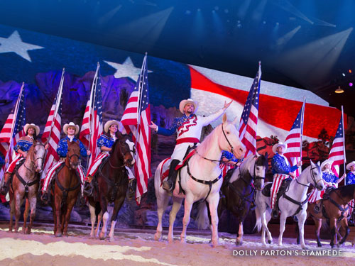 Performers riding horses and holding American flags in a Branson live show.