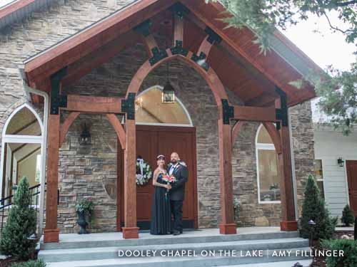 Couple standing in front of a stone chapel after their wedding ceremony.