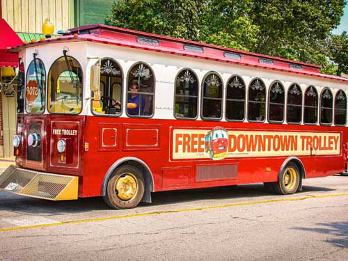 Red free trolley driving through Historic Downtown Branson.