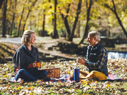 Middle-aged couple sitting on a picnic blanket and eating a picnic at a nature park in Branson.