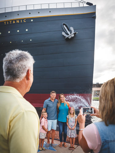 Grandparents taking pictures of their kids and grandkids in front of the Titanic Museum Attraction in Branson.