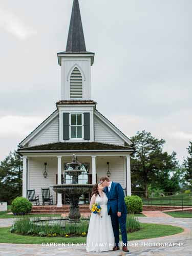 Newlywed couple kissing in front of the Garden Chapel and a large fountain at Big Cedar Lodge.