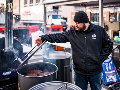 Man cooking barbecue in 55-gallon barrel in Branson.
