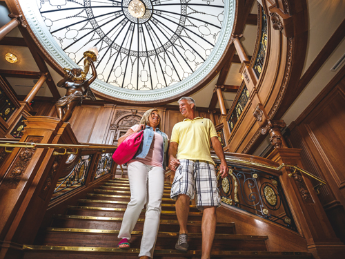 Middle-aged couple walking down the grand staircase at Titanic Museum Attraction in Branson.