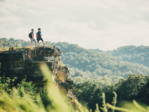 man and woman on a hike standing on the ledge of a scenic pathway in Branson.