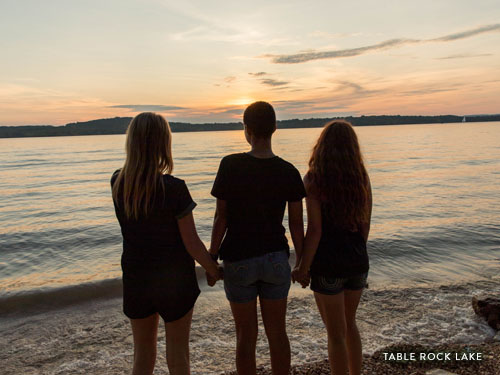 Three girls staring into the sunset at Table Rock Lake.
