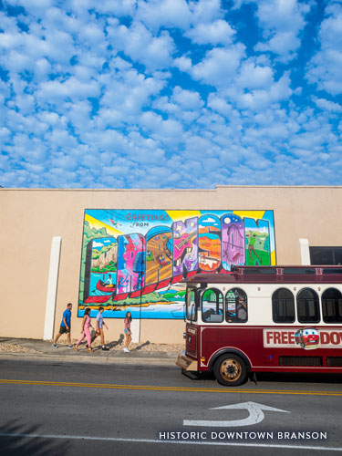 Family of four walking in front of Branson mural while free downtown trolley passes.
