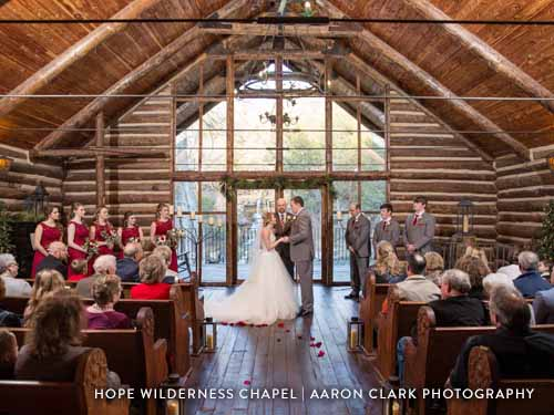Couple going through wedding ceremony with huge glass windows as a backdrop in the chapel.