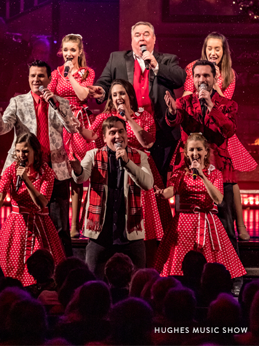 Family performing on a live Branson show stage in match red and white outfits.