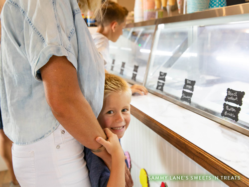 Little blonde headed boy smiling while looking at ice cream with his family.