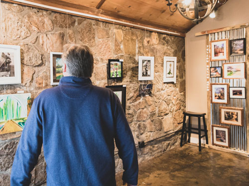 Man walking through art gallery displaying local art from Branson.