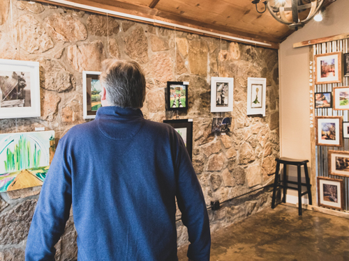 Man walking through art gallery displaying local art from Branson.