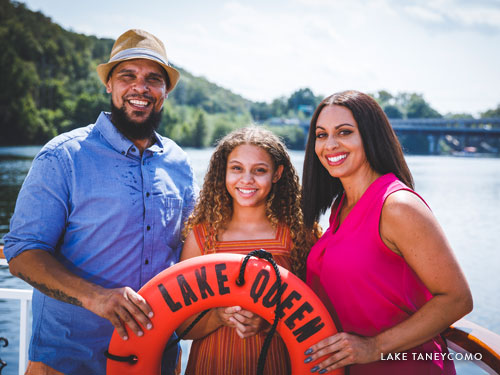 Family of three holding a life ring on a yacht in Branson.