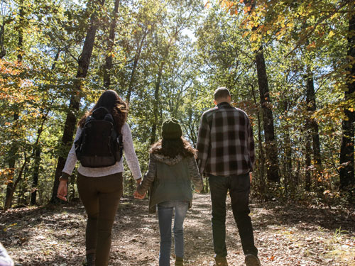 Father, mother and daughter holding hands and walking on wooded hiking trail in Branson.