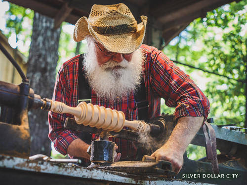 A craftsman at Silver Dollar City creating a wooden piece.